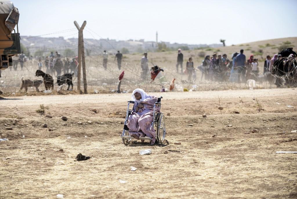 Een oudere vrouw slaapt in haar rolstoel, nadat ze net de grens met Turkije is overgestoken.