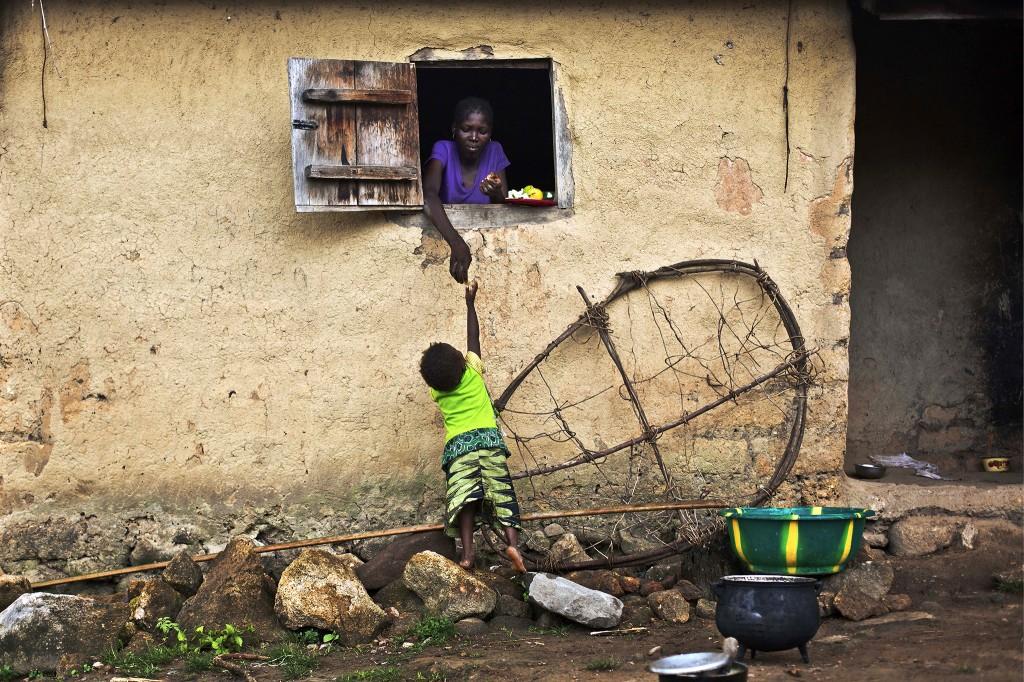 Een kind in Meliandou neemt eten aan van een vrouw.