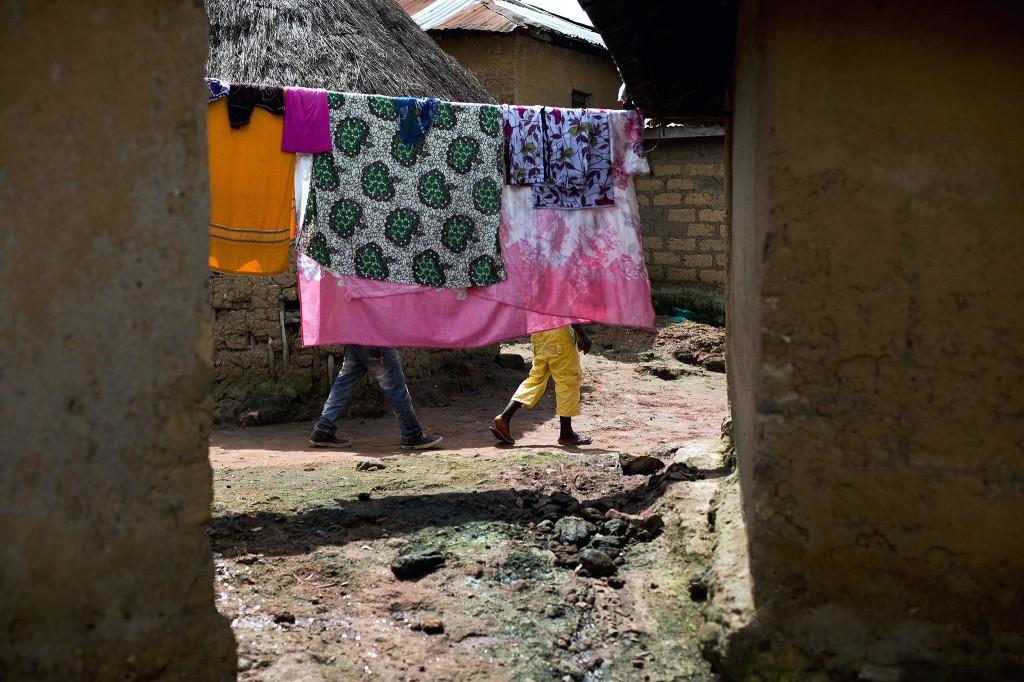 In het dorpje Meliandou hangt de was te drogen. In het dorp gaan allerlei verhalen de ronde over het ontstaan van het ebola-virus. Sommigen geloven bijvoorbeeld dat blanke artsen het virus bewust hebben verspreid onder donkere landgenoten.
