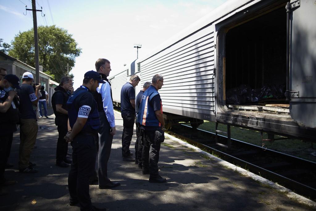Nederlandse experts en de OVSE-medewerkers houden een minuut stilte bij de stoffelijke overschotten van vlucht MH17 . De menselijke resten zijn in gekoelde wagons opgeslagen.