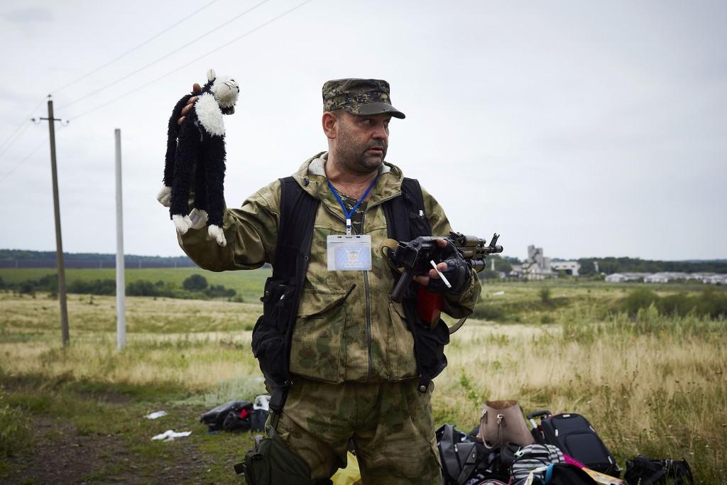 Een van de pro-Russische rebellen houdt de knuffel van een slachtoffer omhoog op de rampplek.