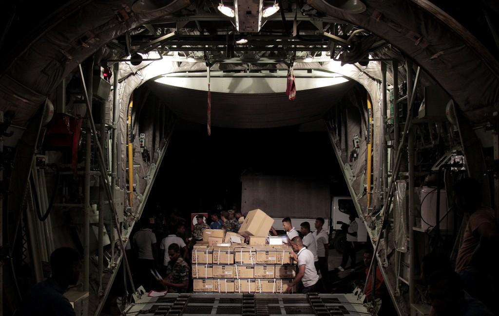 Medewerkers van de luchtmacht van Sri Lanka laden noodpakketten in een vliegtuig. Het toestel, dat vertrekt vanaf de internationale luchthaven in Katunayake (Sri Lanka), vliegt naar het door de aardbeving getroffen gebied in Nepal.