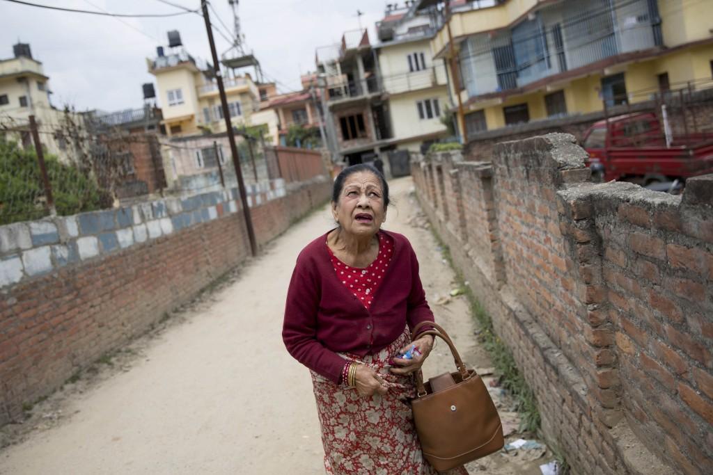 Een oudere vrouw loopt op straat tijdens een naschok.