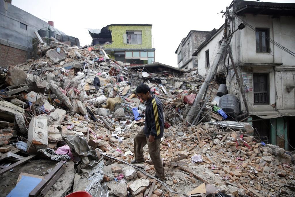 Een man bekijkt de brokstukken van een ingestort gebouw, een dag na de aardbeving.