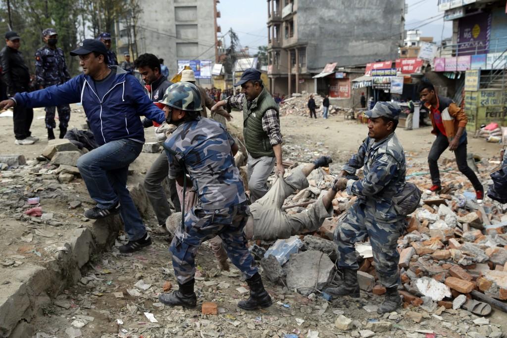 Reddingswerkers verzamelen dode lichamen, gevonden tussen het puin.