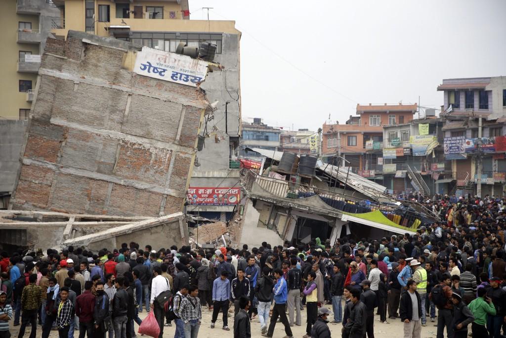 Inwoners van Nepal verzamelen rond de ingestorte gebouwen om te rouwen.