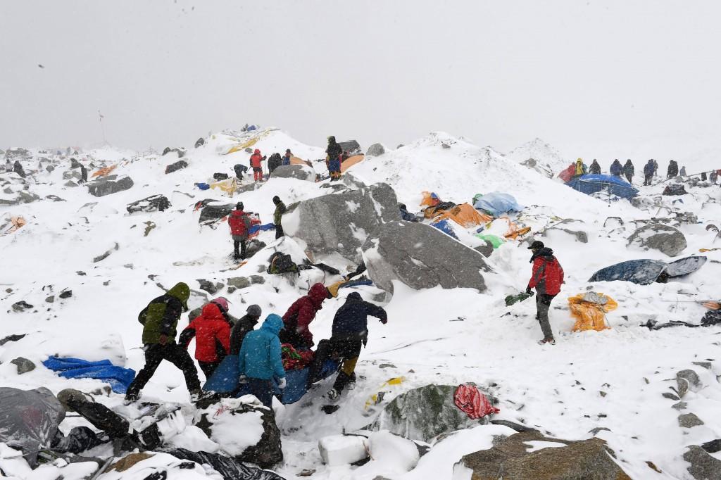 Reddingswerkers dragen een gewonde klimmer, die geraakt is door een lawine op de Mount Everest.