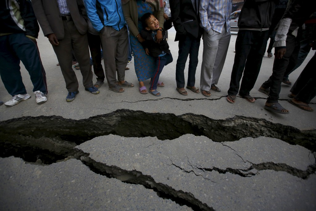 Mensen verzamelen bij de scheuren in de weg, veroorzaakt door de aardbeving.