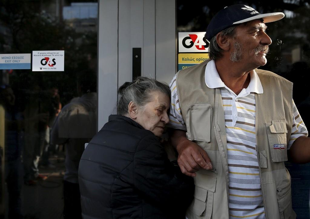 Een 75-jarige Griekse vrouw, Vallia (l), staat in Athene aan de deur van de Griekse centrale bank in de hoop haar pensioen te krijgen.