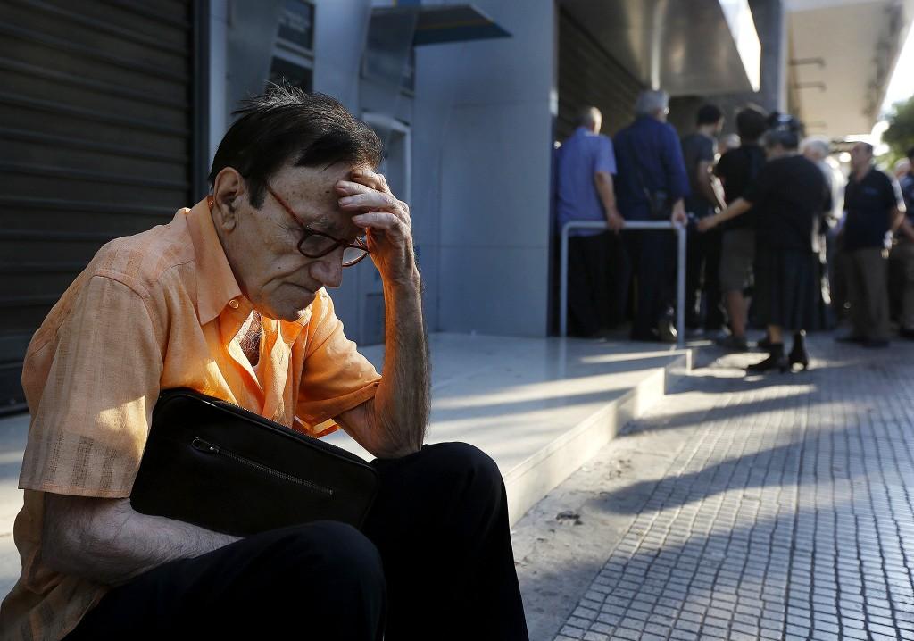 De 77-jarige Giorgos, een pensionado in Athene, wacht op de stoep bij de Griekse centrale bank, in de hoop zijn pensioen voor deze week nog te krijgen.