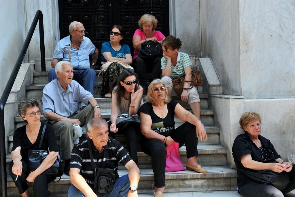 Voor de vestiging van een Griekse bank wachten inwoners van Thessaloniki in de hoop dat de deuren opengaan.