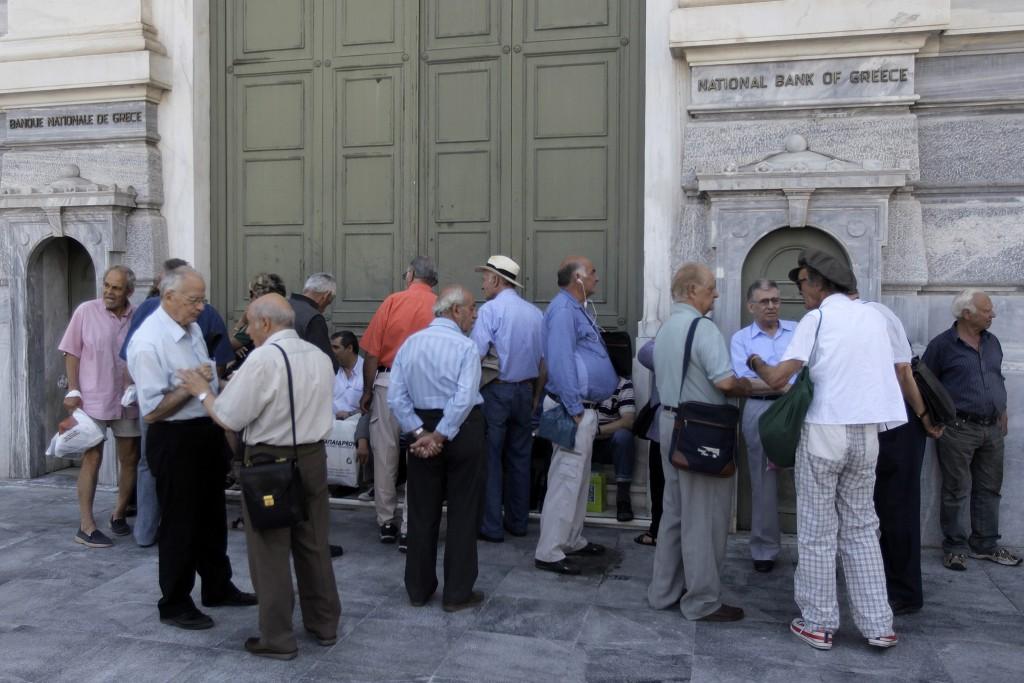 Een groep mensen, onder wie gepensioneerden zonder pinpas, wachten in Athene voor de deur van een vestiging van de Griekse centrale bank.