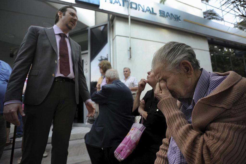 Op de stoep van een vestiging van de Griekse centrale bank legt een bankmedewerker aan een groep gepensioneerden uit wanneer zij weer hun pensioen kunnen verwachten.