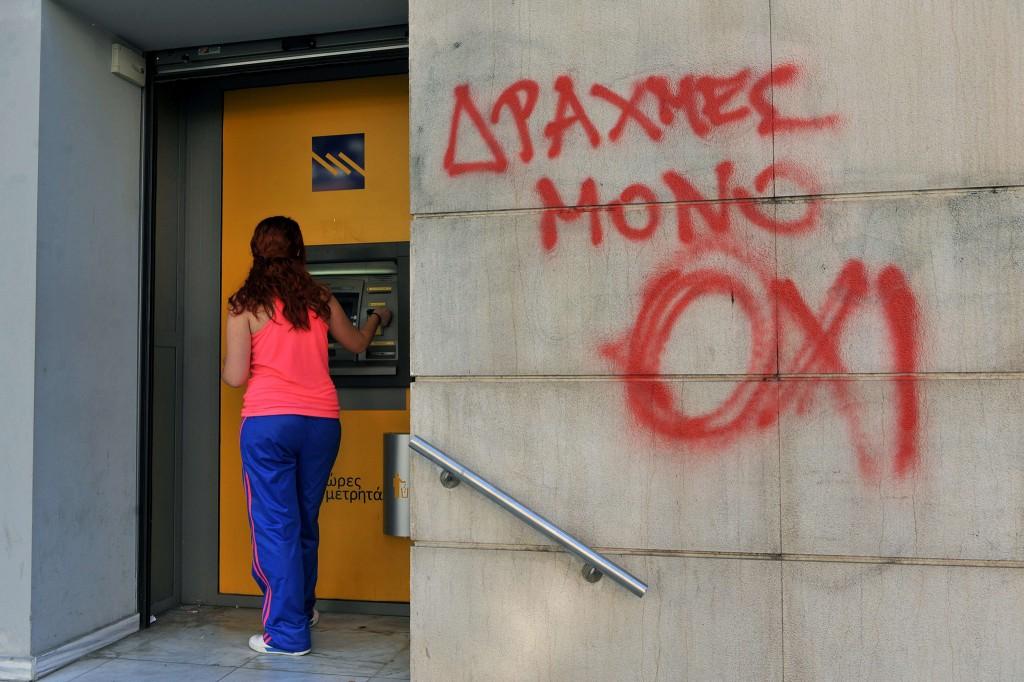"""Een vrouw bij een Grieks pinautomaat. Op de muur staat: """"Enkel drachme, NO""""."""