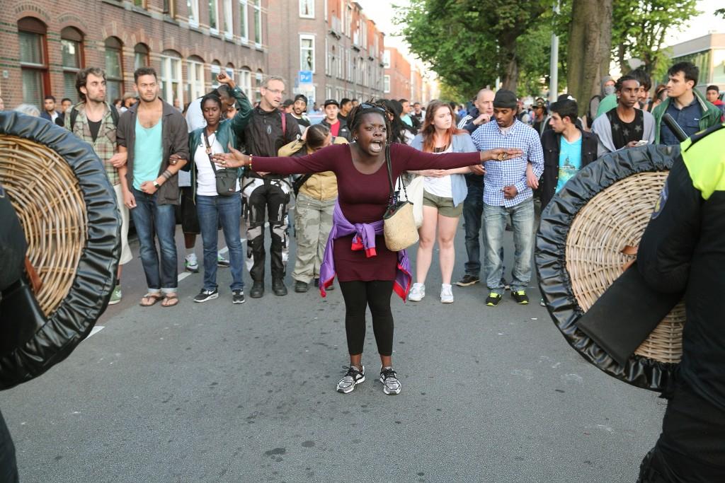 Een demonstrant is woedend en uit haar frustratie tegen de opgetrommelde Mobiele Eenheid (ME)