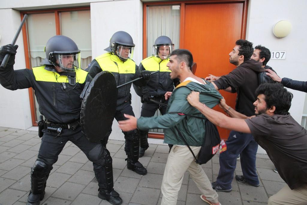 De ME en een paar demonstranten proberen betogers tegen te houden die het politiebureau willen bestormen.