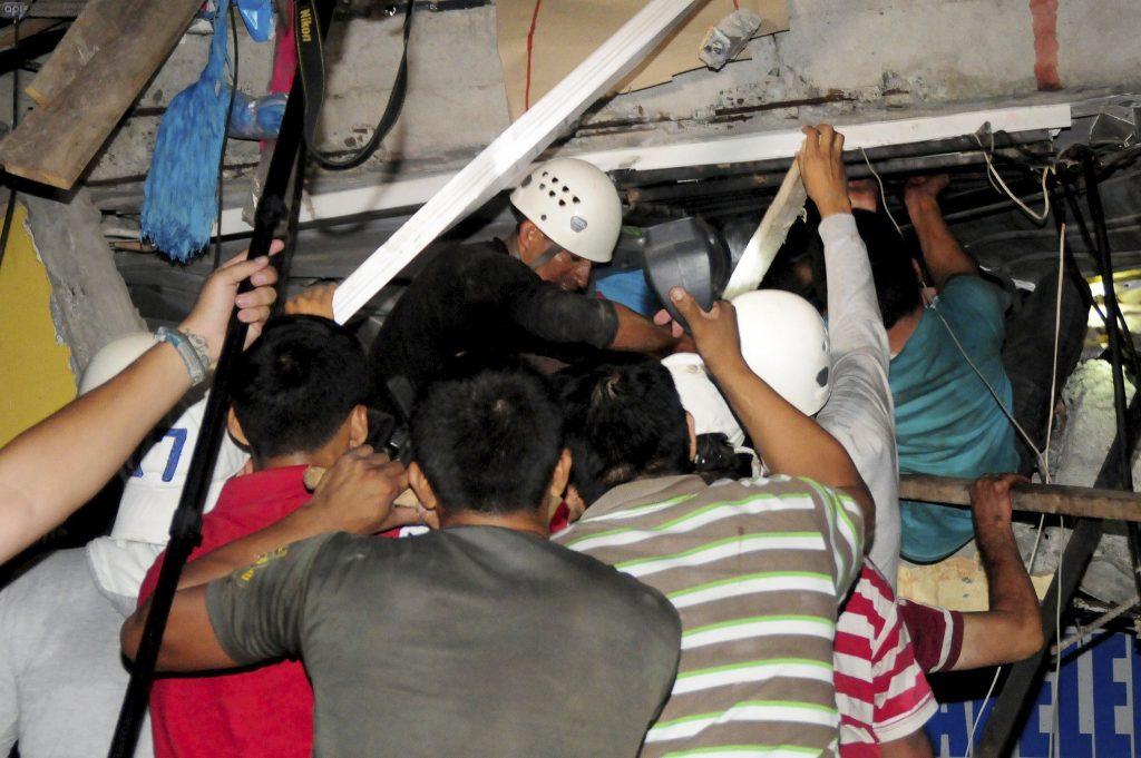 Reddingswerkers proberen overlevenden uit een ingestort gebouw in de stad Manta te halen.