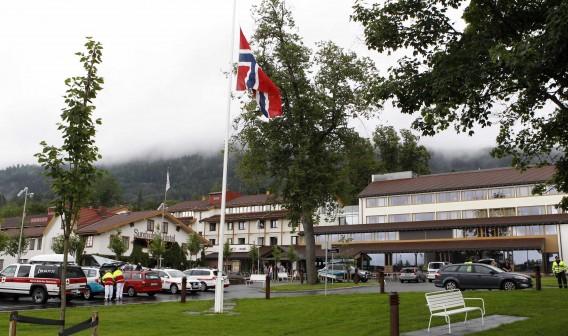 De vlag van Noorwegen hangt halfstok voor het hotel waar slachtoffers van de schietpartij op het eiland verblijven. Foto Reuters / Fabrizio Bensch