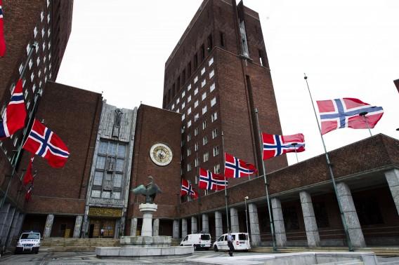 De vlaggen hangen halfstok bij het gemeentehuis van Oslo, vandaag. Foto AFP / Roals Berit