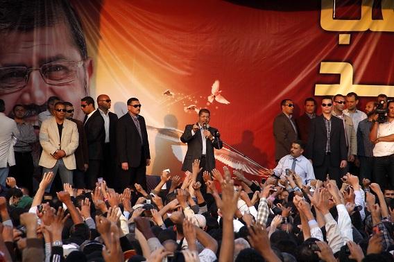 """Morsi sprak vandaag aanhangers toe voor het Presidentieel Paleis in Kairo. Hij zei dat Egypte """"voorwaarts"""" moet en dat tegenstanders geen zorg voor hem zijn, maar dat het tijd wordt voor een echte en sterke oppositie. Foto AP / Aly Hazaza"""